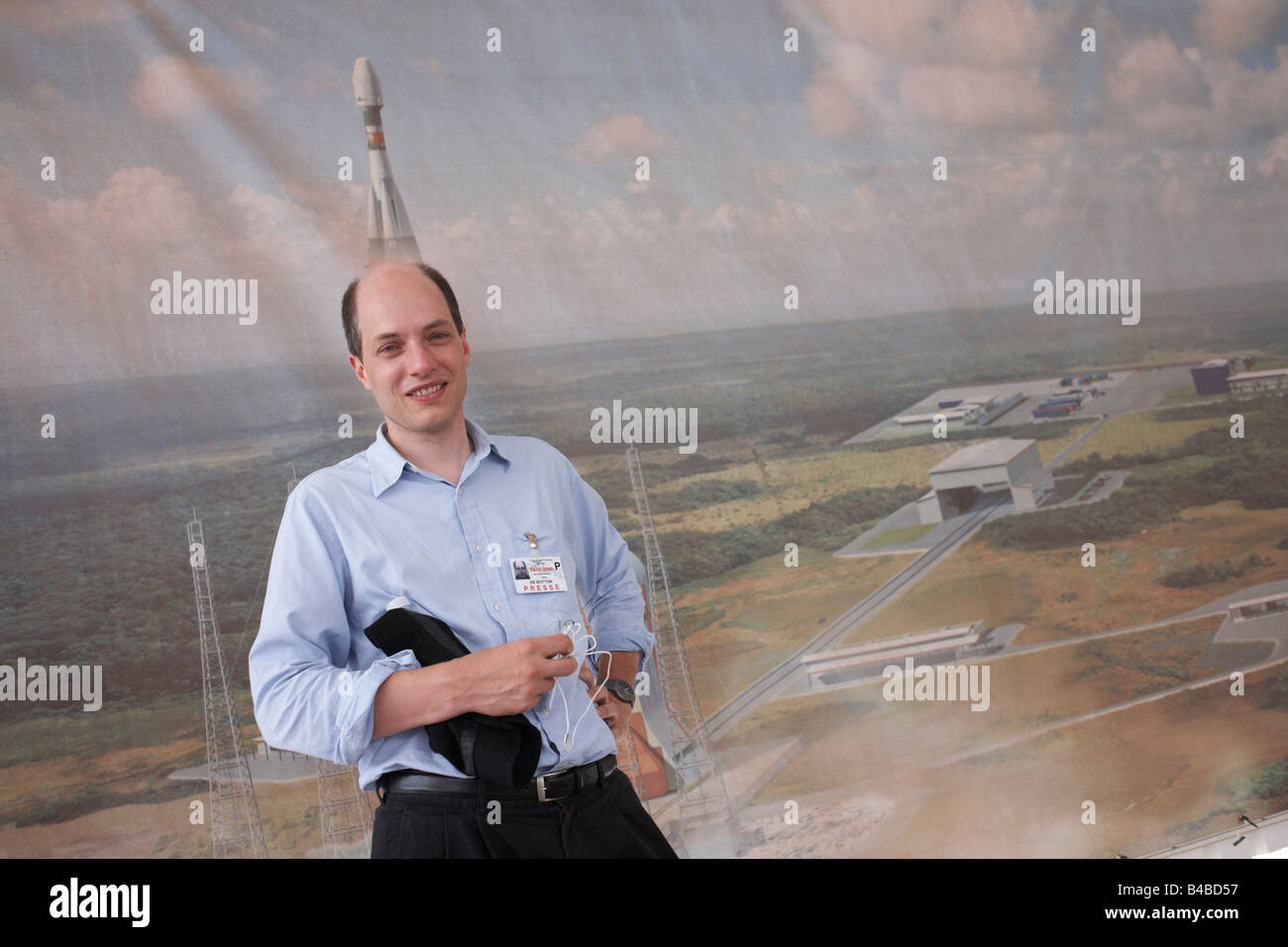 Writer Alain de Botton stands by a mural of a launching Roskosmos Soyuz rocket while researching at ESA's Kourou - Stock Image
