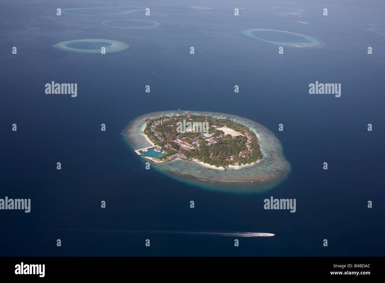 Aerial view of a passing boat and one of 1,192 inhabited and deserted coral islands in the Islamic Republic of Maldives Stock Photo
