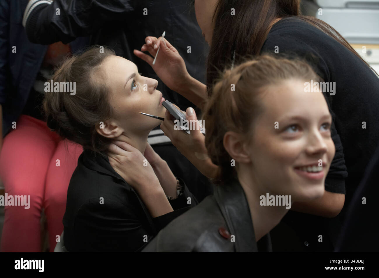 Make-up and hair stylists ready models at  British couture designer Margaret Howell's Autumn fashion show in - Stock Image