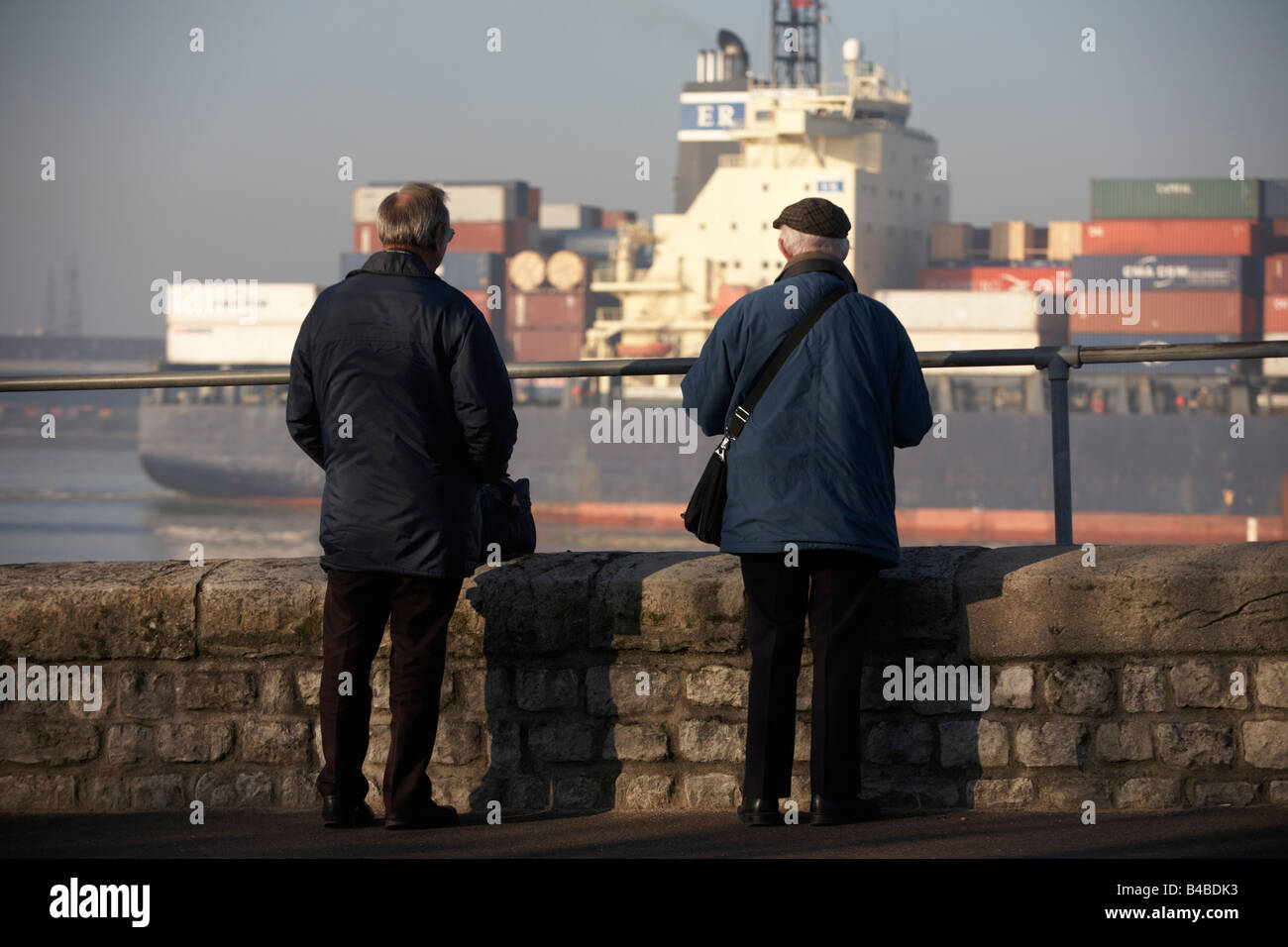 The cargo ship 'CMA CGM Turkey' eases past two elderly ship spotters who log its details on the River Thames - Stock Image