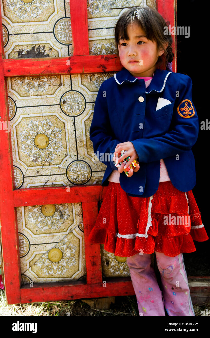 A cute Mongolian girl stands in the entrance to her family's traditional home called GER or YURT - Stock Image