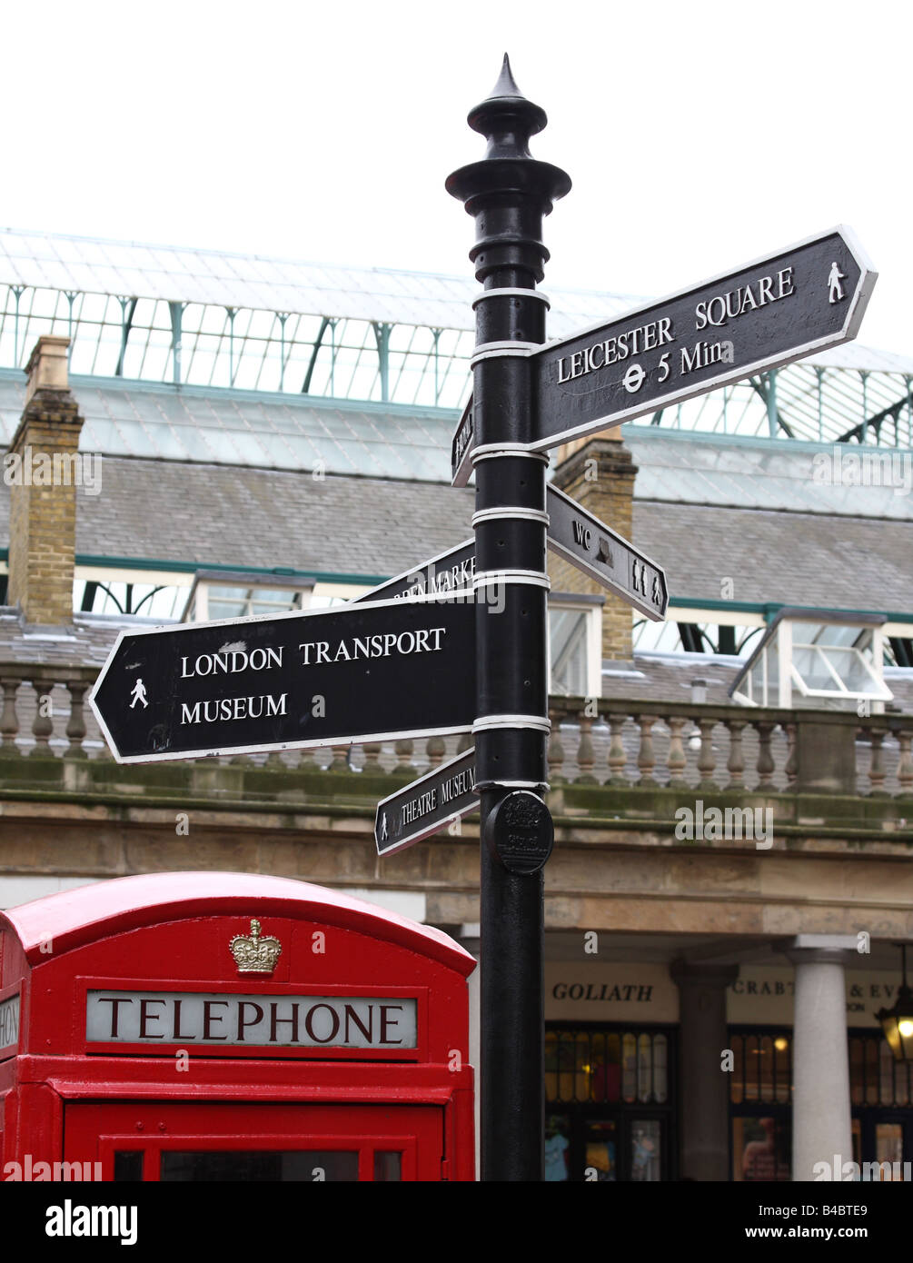 A traditional red telephone box and street sign in Covent Garden, London, England, U.K. - Stock Image