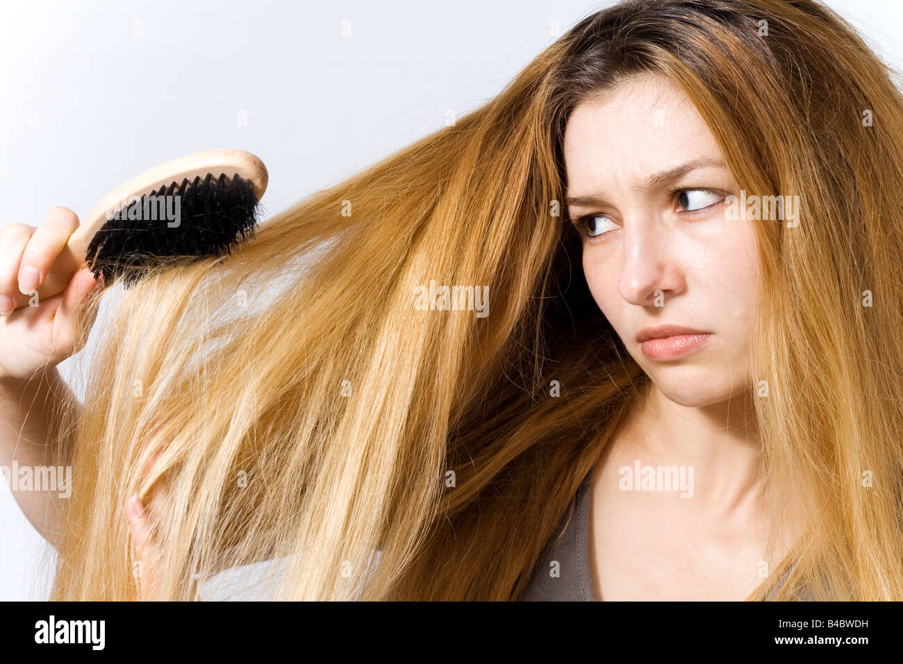 Young woman with hairbrush worried by her tangled hair - Stock Image