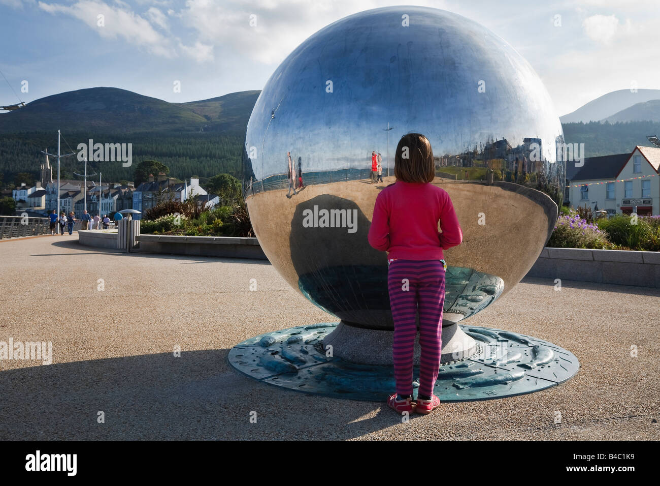 Child looking at her reflection in 'Global Journeys', a sculpture by Chris Wilson on Newcastle promenade, - Stock Image