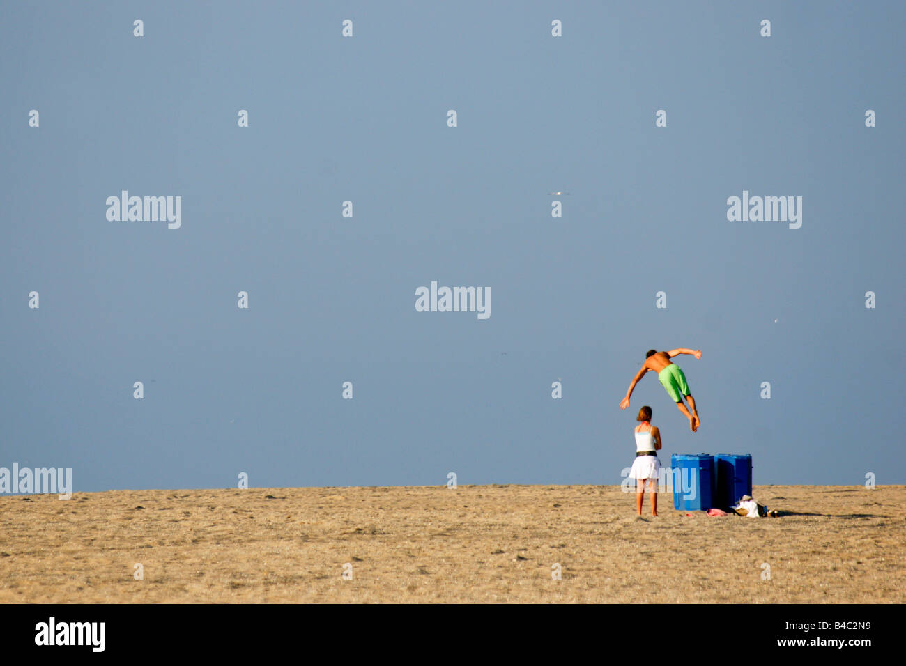 Man trying impress woman bare chest at sand beach under blue sky Hoek van Holland Netherlands alone empty abandoned - Stock Image