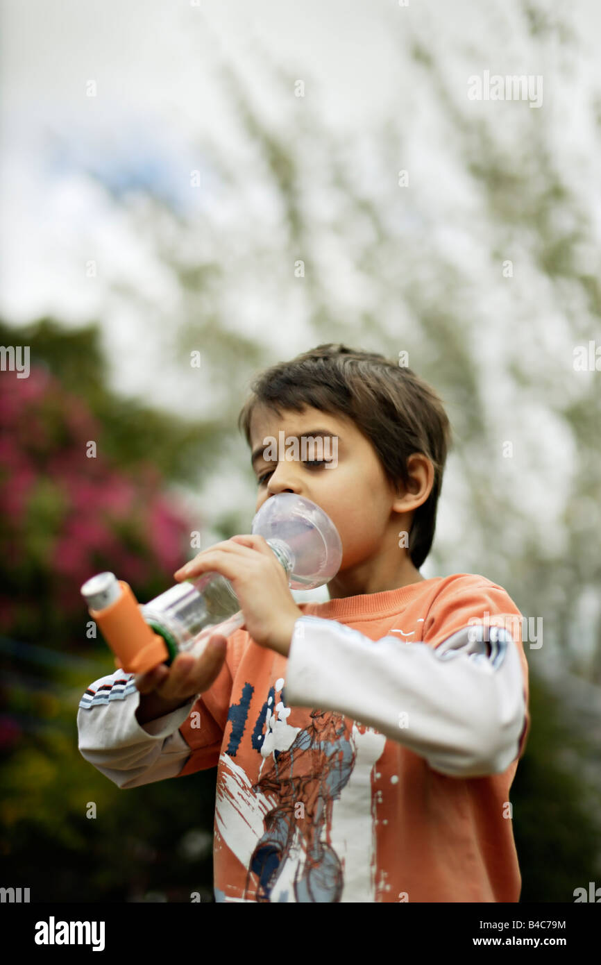 Asthmatic six year old boy with inhaler - Stock Image