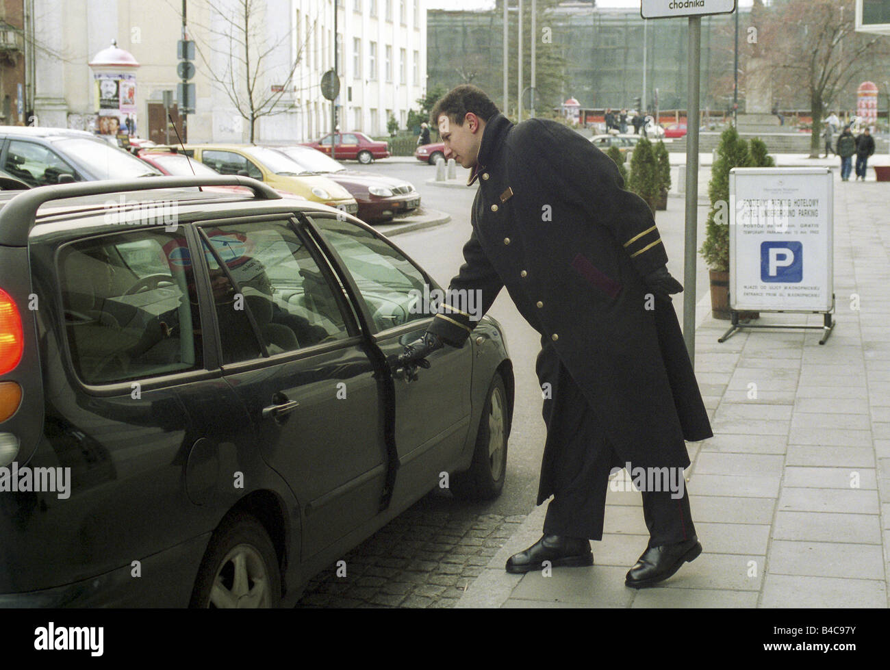 A doorman of the Sheraton Hotel opening the car door for a guest, Warsaw, Poland - Stock Image