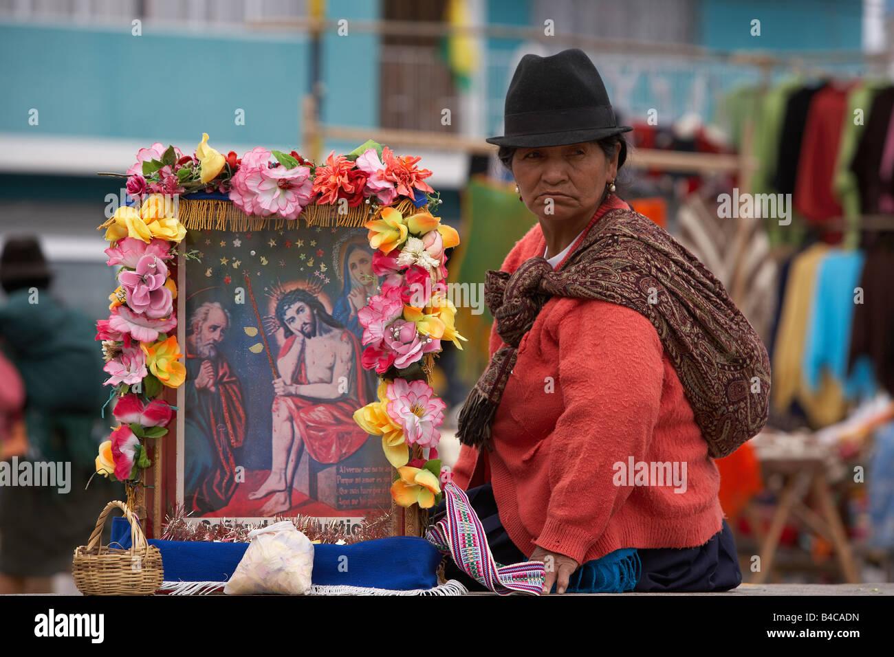 Woman with religious picture, Saquisili Market, Andes Mountains, Ecuador - Stock Image