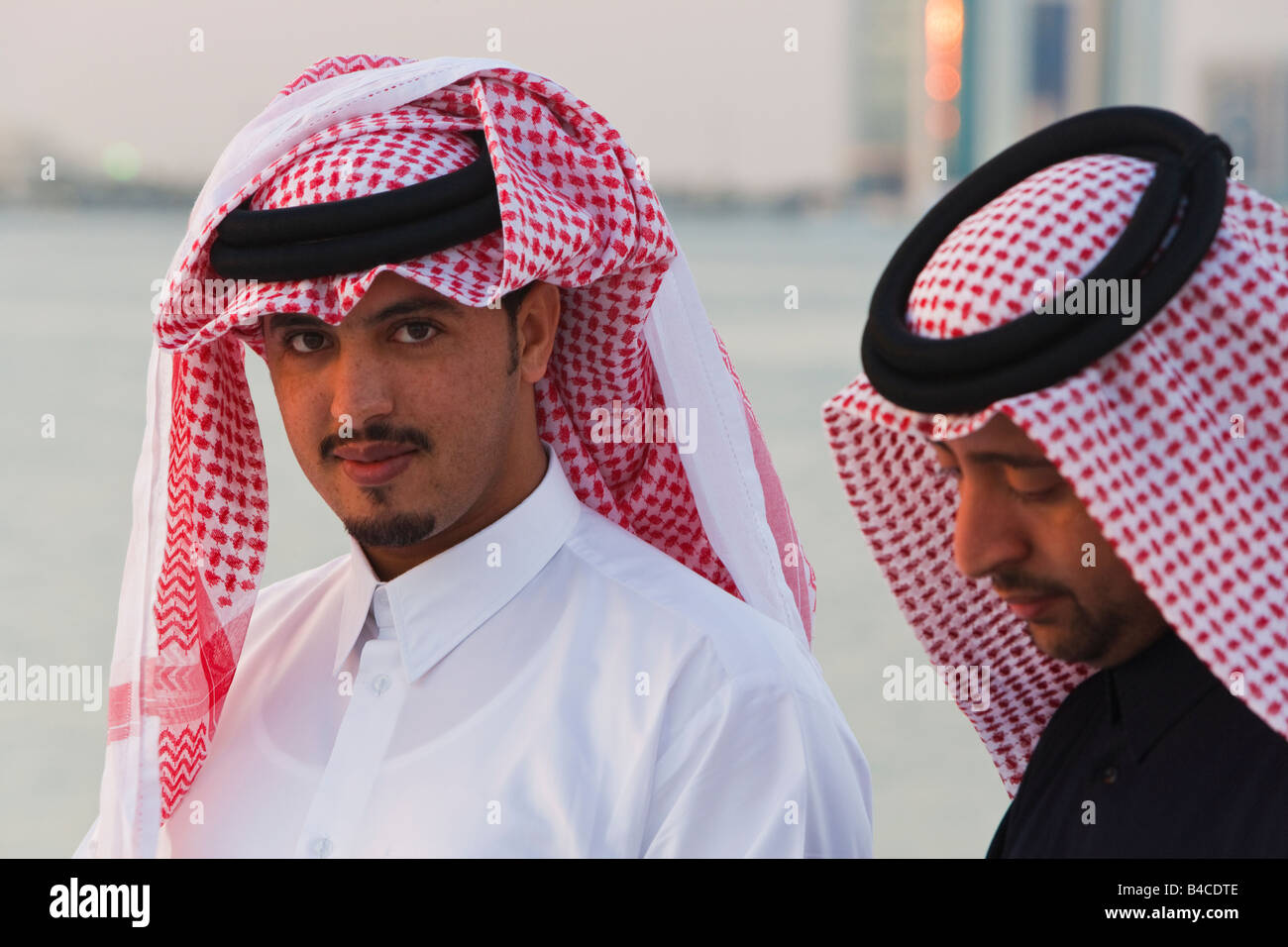 Qatar, Middle East, Arabian Peninsula, Doha, two men wearing traditional dress of thobe floor length shirt dress - Stock Image