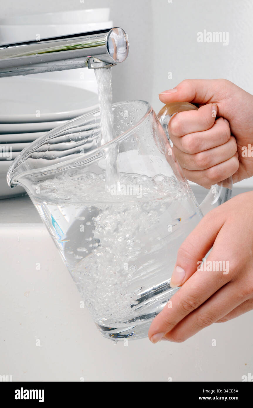 WOMAN FILLING JUG WITH TAP WATER - Stock Image