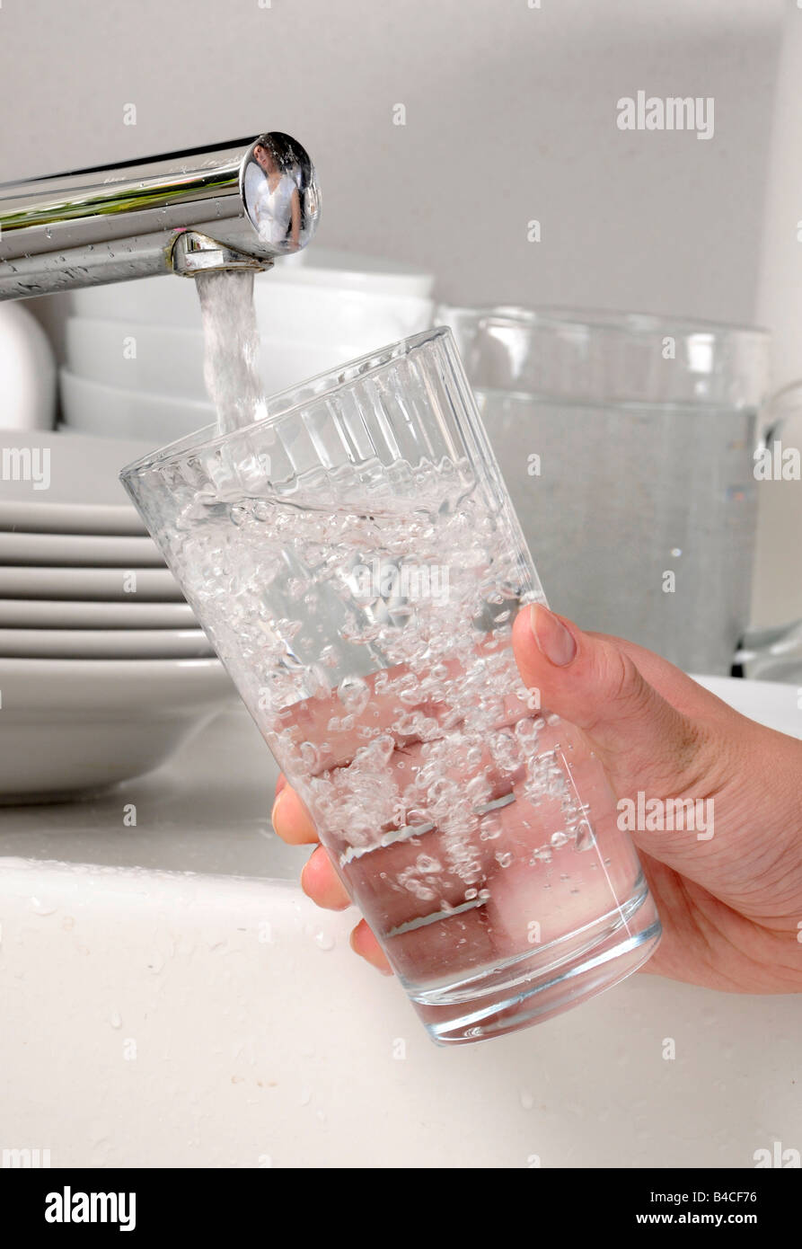WOMAN FILLING GLASS TUMBLER WITH TAP WATER - Stock Image