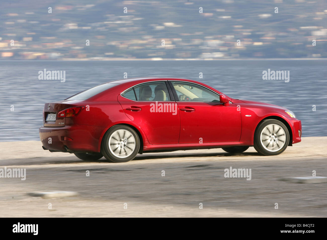 Lexus IS 250, model year 2005-, red, driving, side view, lake - Stock Image