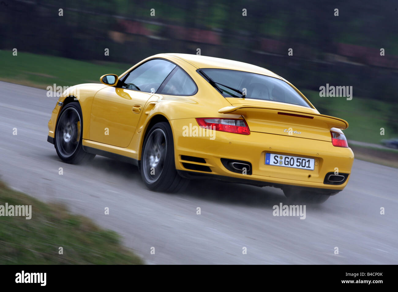 Porsche 911 turbo, model year 2006-, yellow, driving, diagonal from the back, rear view, country road - Stock Image