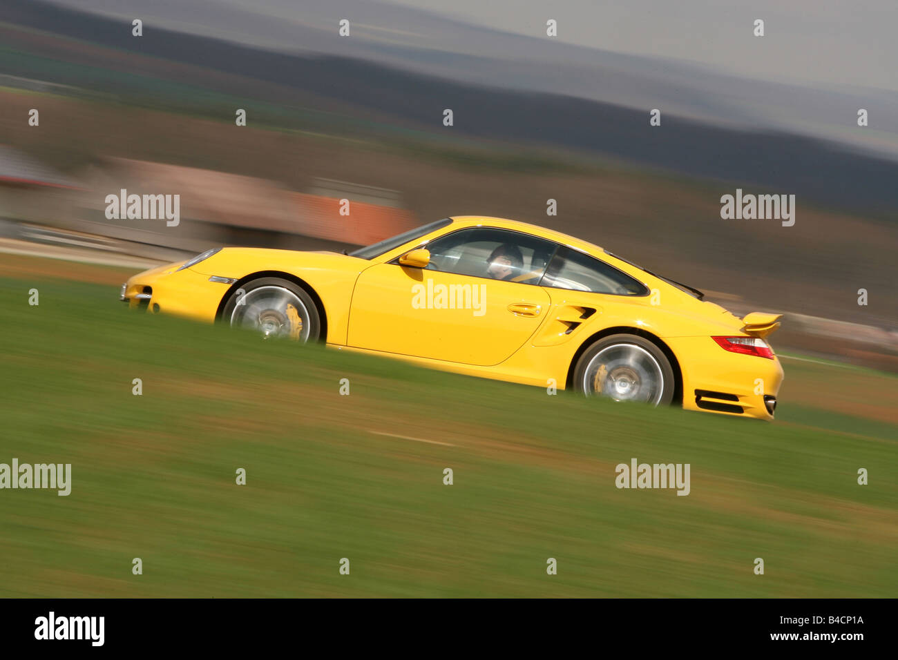 Porsche 911 turbo, model year 2006-, yellow, driving, side view, country road - Stock Image