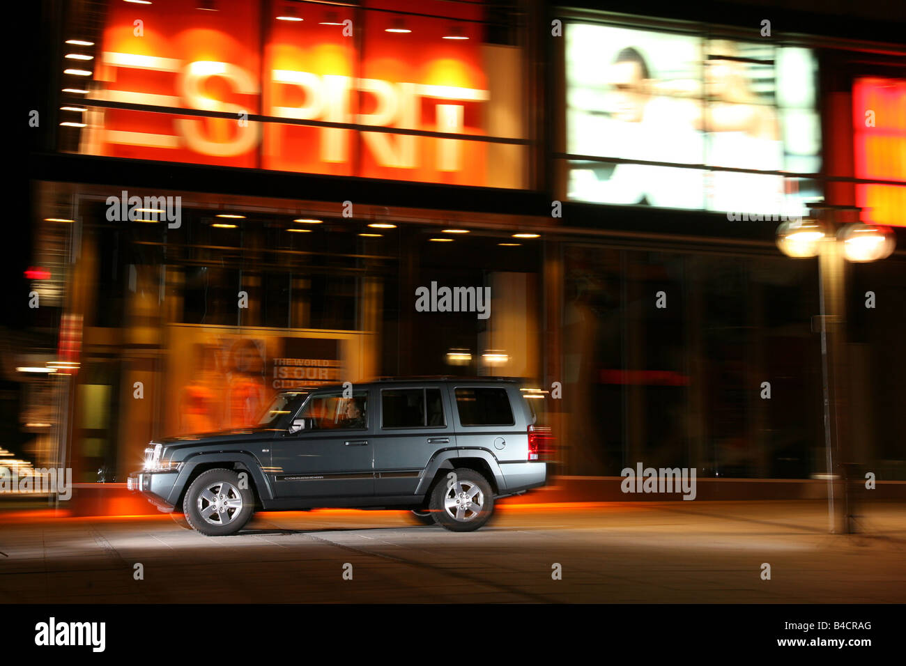 Jeep Commander 3.0 CRD, model year 2006-, silver, driving, side view, City, night shot, Evening - Stock Image