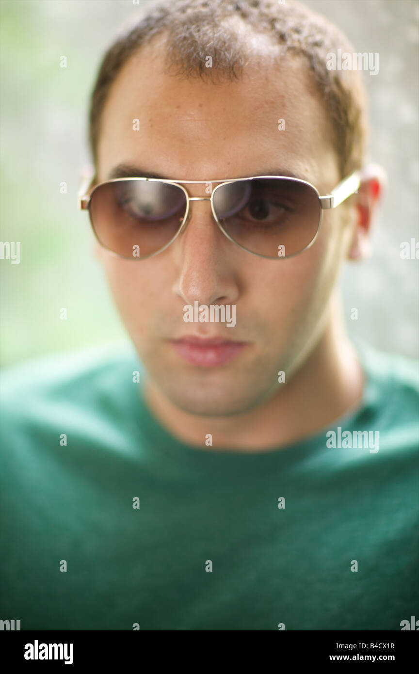 Stunning portrait of a crosseyed balding white man having trouble focusing, because he's wearing his wife's aviator Stock Photo
