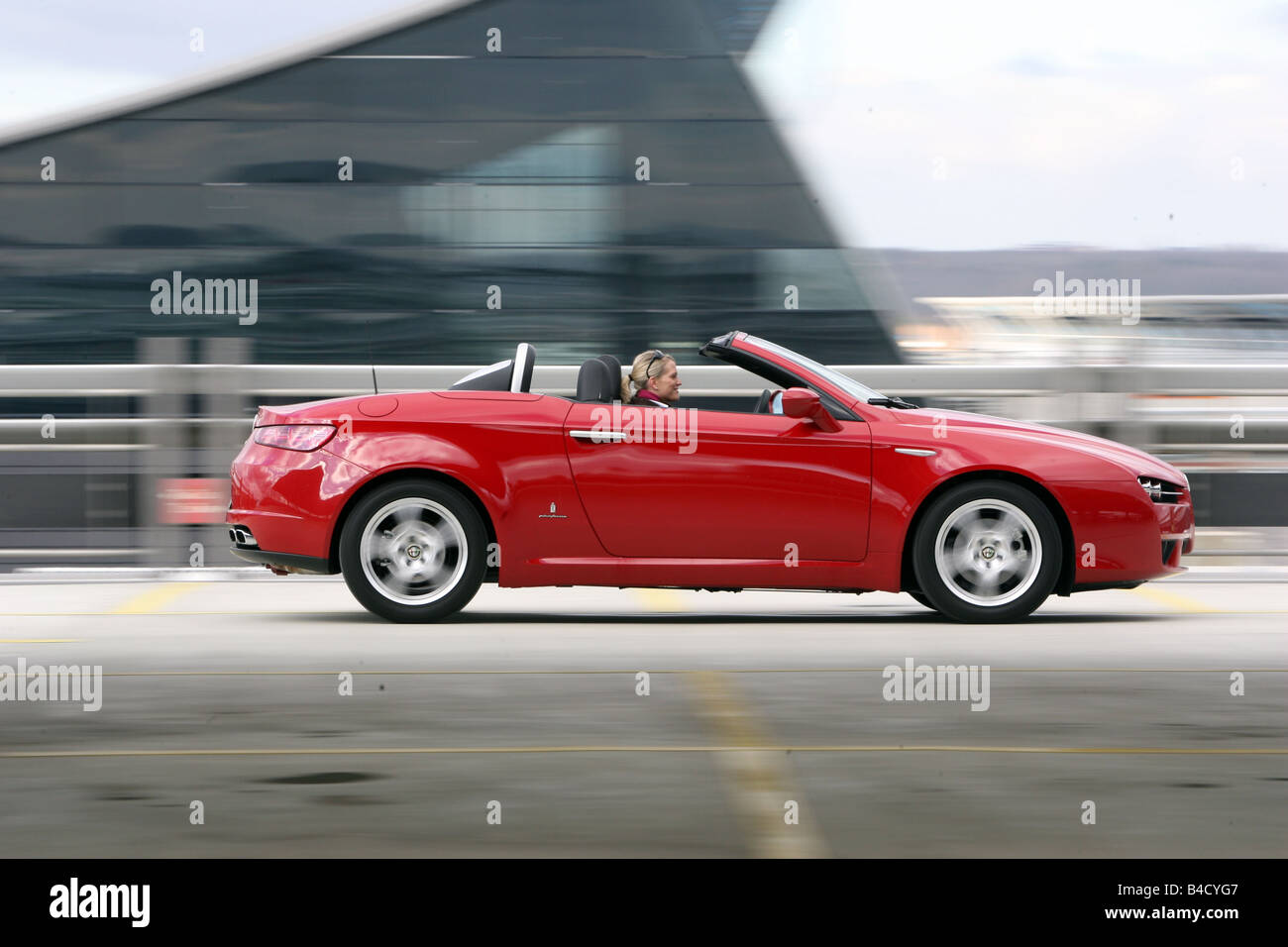 Alfa Romeo Spider 2.2 JTS Exclusive, model year 2007-, red, driving, side view, open top - Stock Image