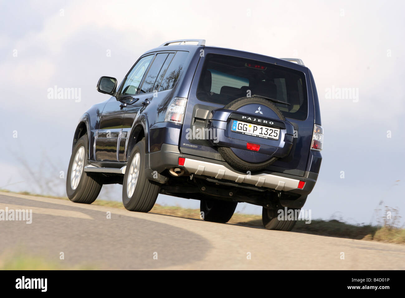 Mitsubishi Pajero 3,2 Instyle-Version, model year 2007-, dunkelblue moving, diagonal from the back, rear view, country - Stock Image