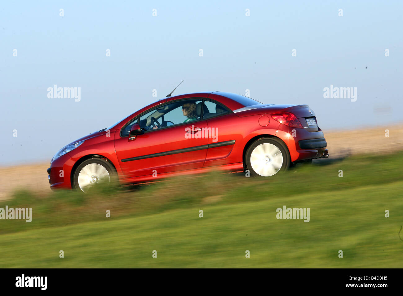 Peugeot 207 CC, model year 2007-, red, driving, side view, country road, closed top Stock Photo