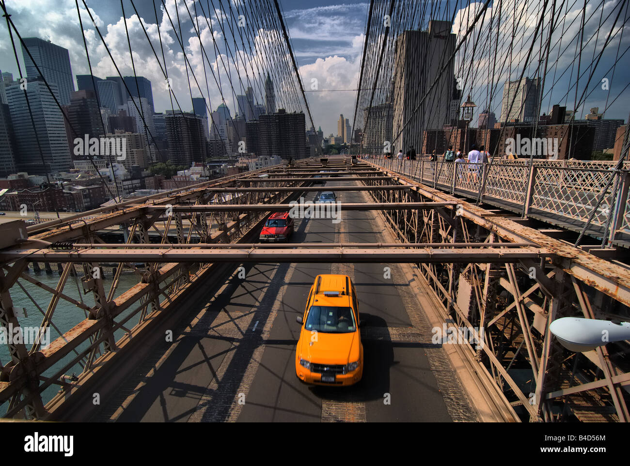 A taxi is among the traffic crossing the Brooklyn Bridge.  Pedestrians can also be seen on the upper walkway. - Stock Image