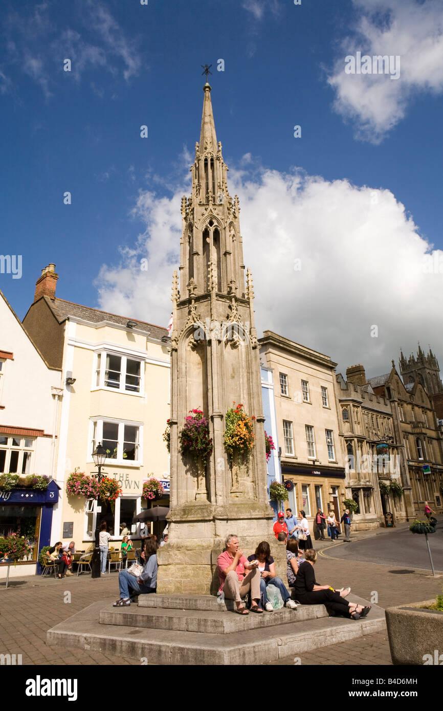 UK England Somerset Glastonbury Market Place visitors sat on base of cross in sunshine - Stock Image