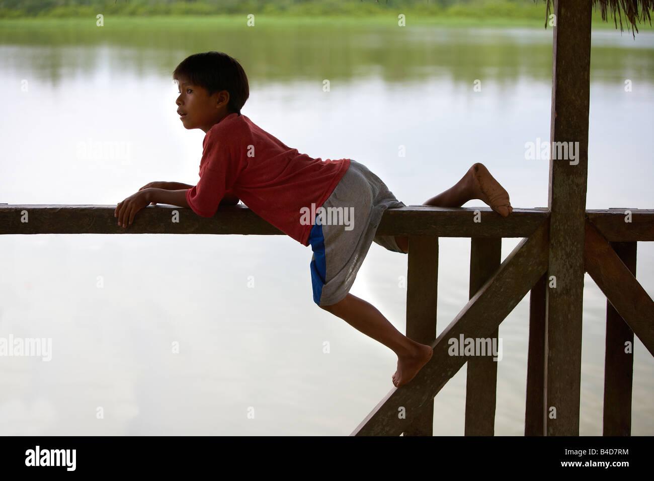 Boy on post Napo River, Amazon Rain Forest, Ecuador - Stock Image