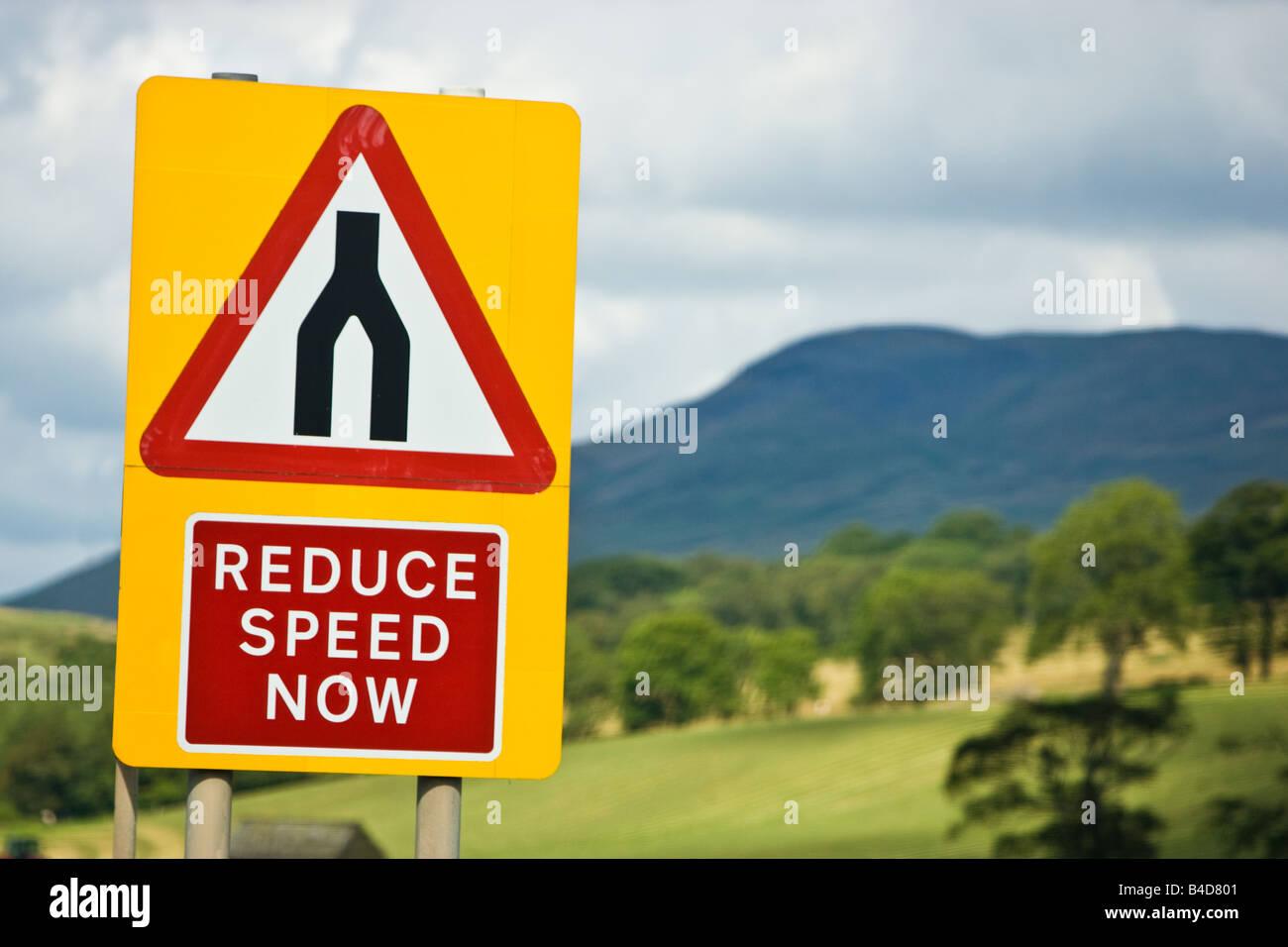Road sign warning sign of dual carriageway ending speed reduction, roads merge advised, England UK - Stock Image