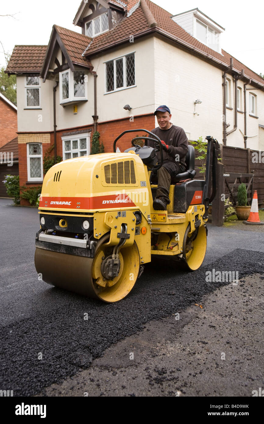 Home improvements worker hot rolling new tarmac domestic drive tarmacadam flat Stock Photo
