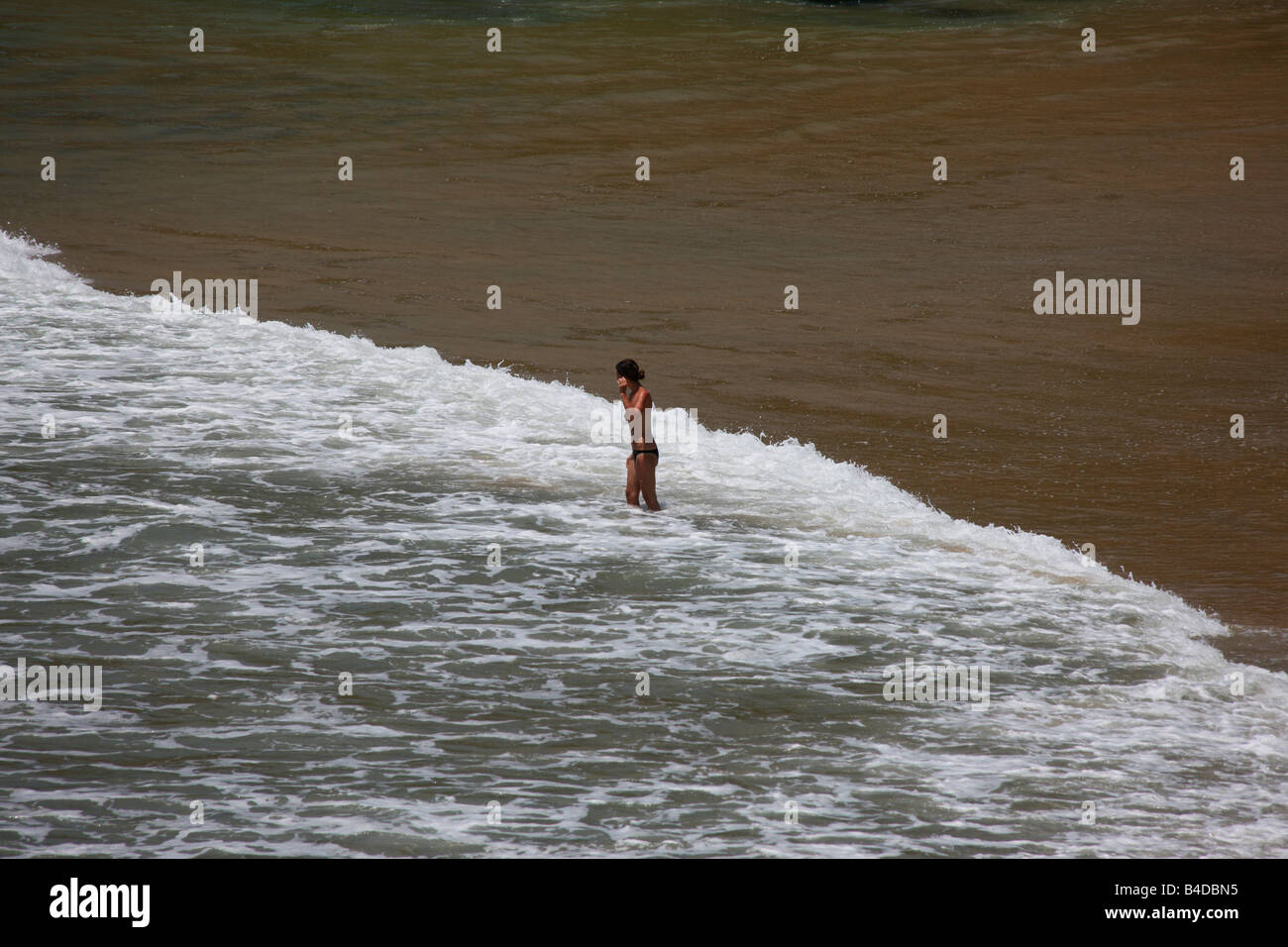 A woman on a beach enjoying the sea froth - Stock Image