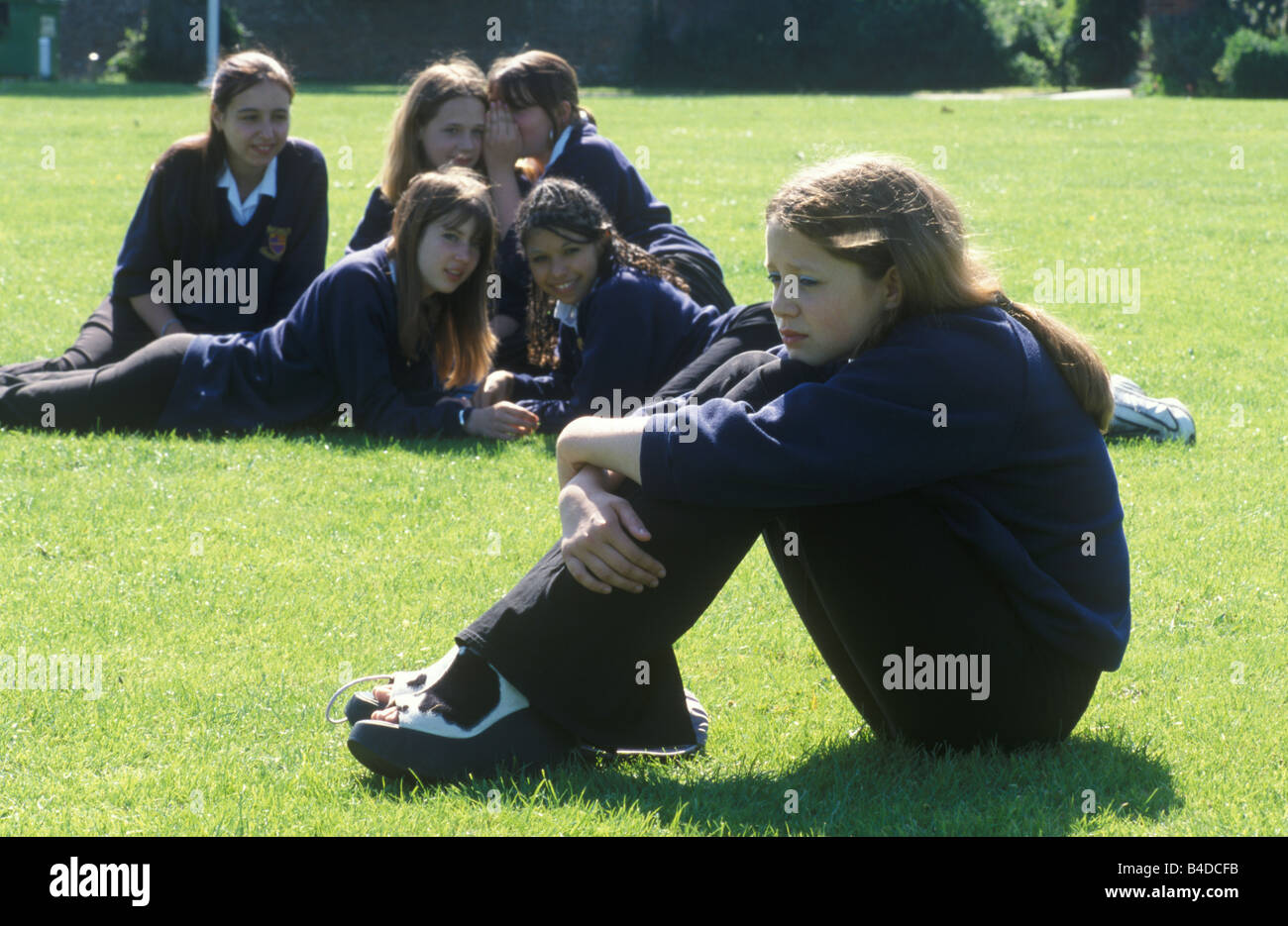 isolated pupil sitting outside school being taunted by peers - Stock Image