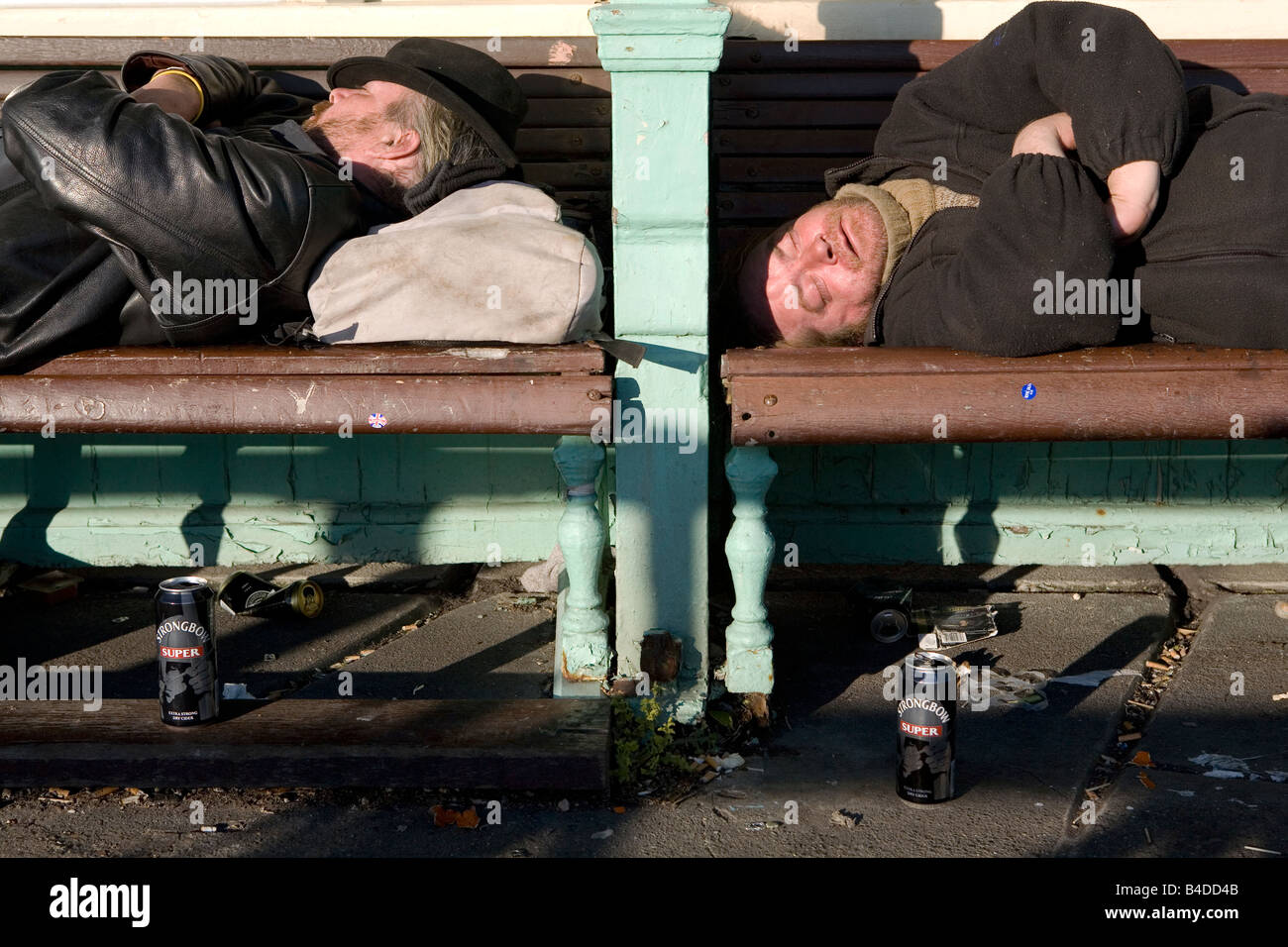 Two homeless men sleeping on a bench Stock Photo