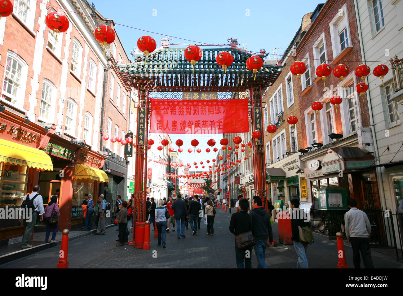 Tourists pass under the main red gateway entrance to China Town in London's West End area England UK - Stock Image
