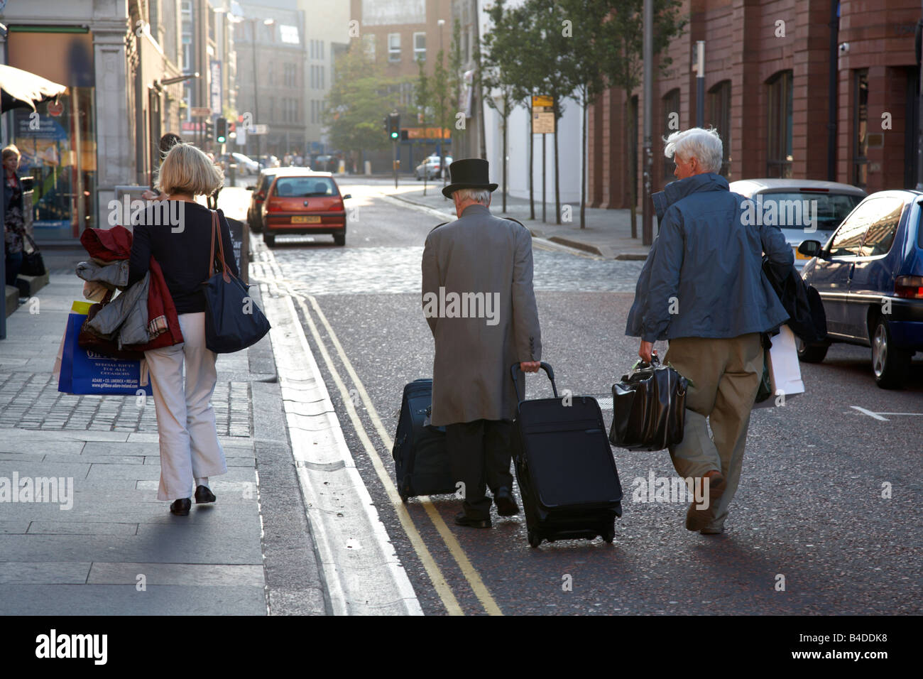 hotel concierge with guests luggage leading guest down a street - Stock Image