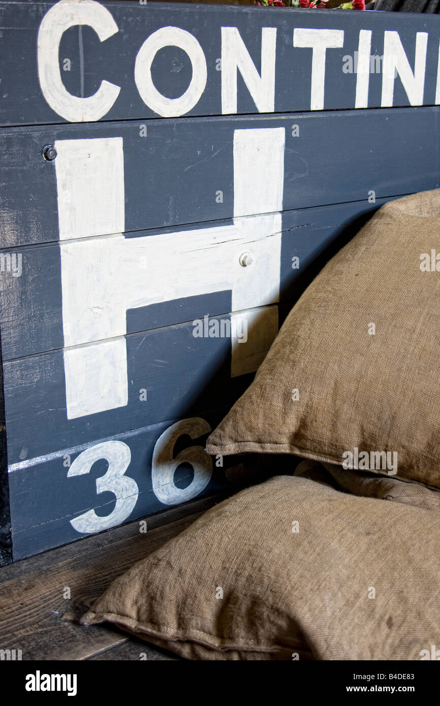Sacks piled in front of wooden crate - Stock Image