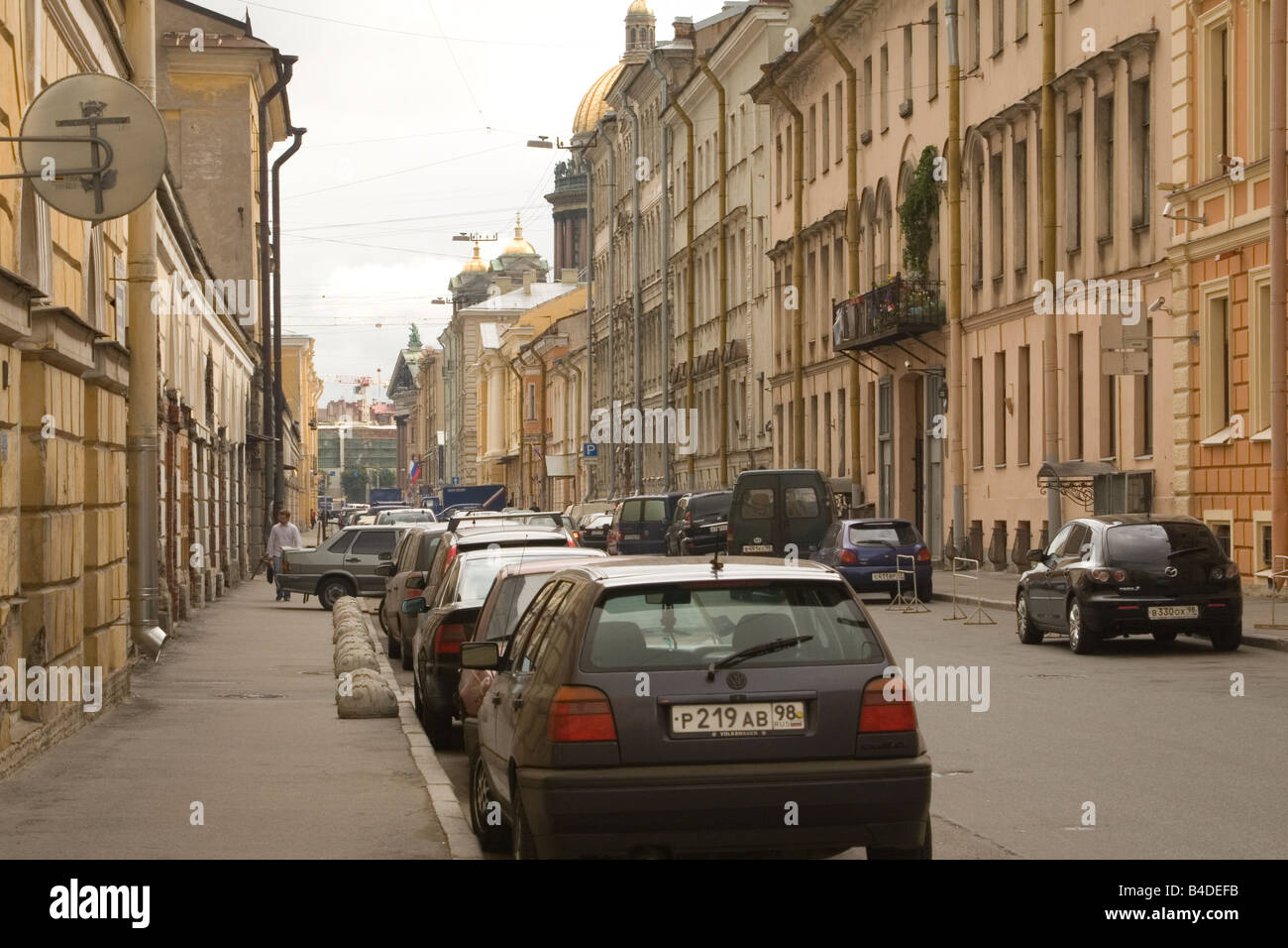 Street in St. Petersburg is lined with parked vehicles. - Stock Image