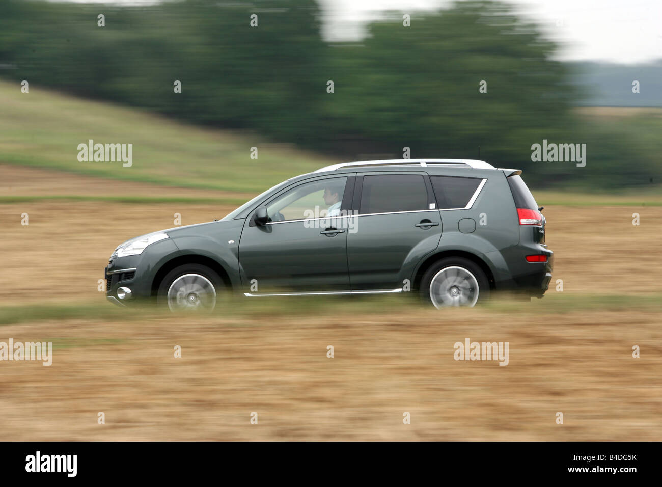 Citroen C-Crosser HDi 155 FAP Exclusive, model year 2007- anthracite, driving, side view, country road - Stock Image