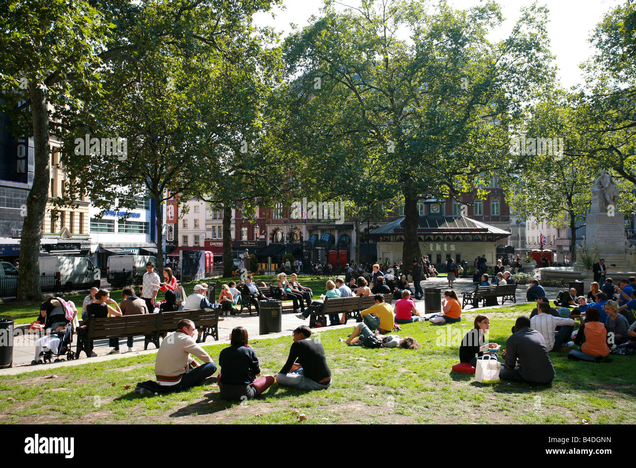 Tourists and students enjoy sunshine relaxing on grass in Leicester Square London West End theatre entertainment Stock Photo