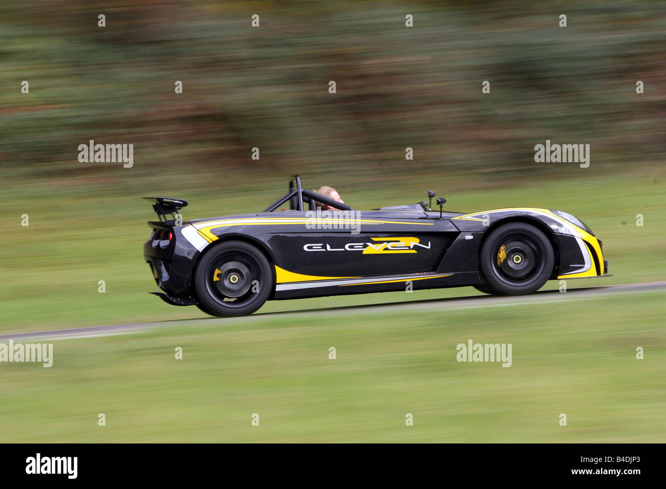Lotus 2-Eleven, model year 2007-, black-yellow, driving, moving, side view, country road - Stock Image