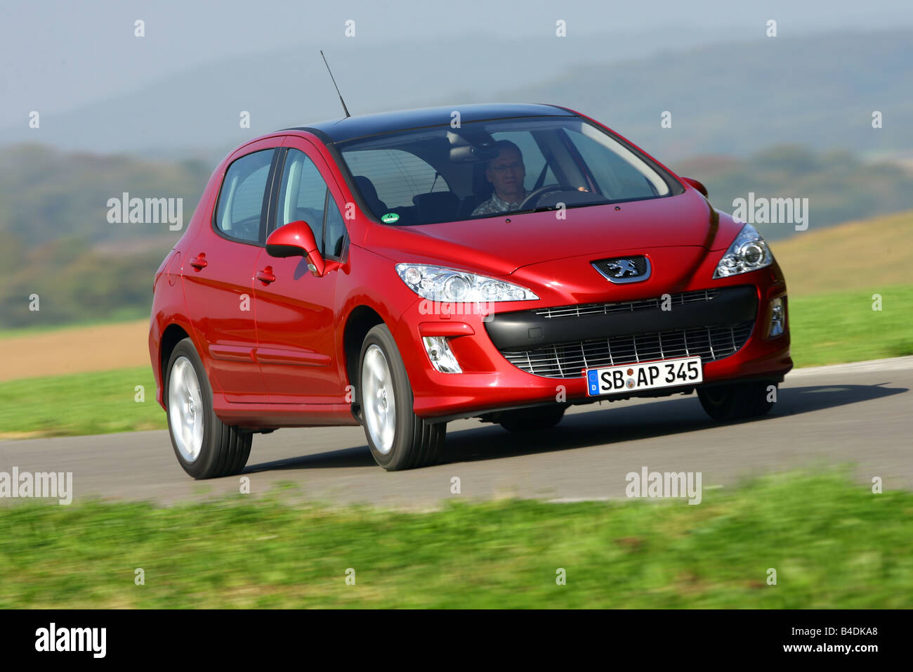 Peugeot 308 150 THP Sport Plus, model year 2007-, red, driving, diagonal from the front, frontal view, country road - Stock Image