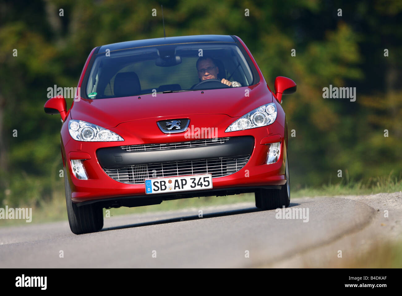 Peugeot 308 150 THP Sport Plus, model year 2007-, red, driving, diagonal from the front, frontal view, country road Stock Photo