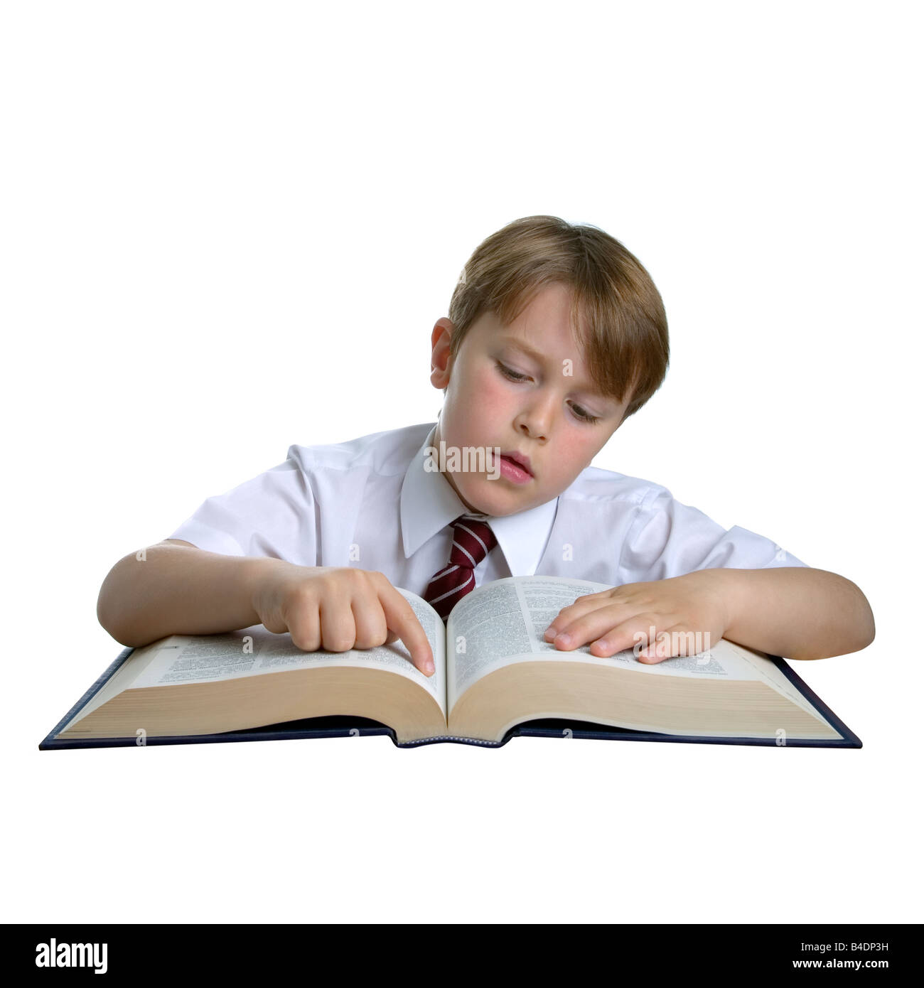 Cut out of a schoolboy reading a reference book whilst doing his school homework - Stock Image