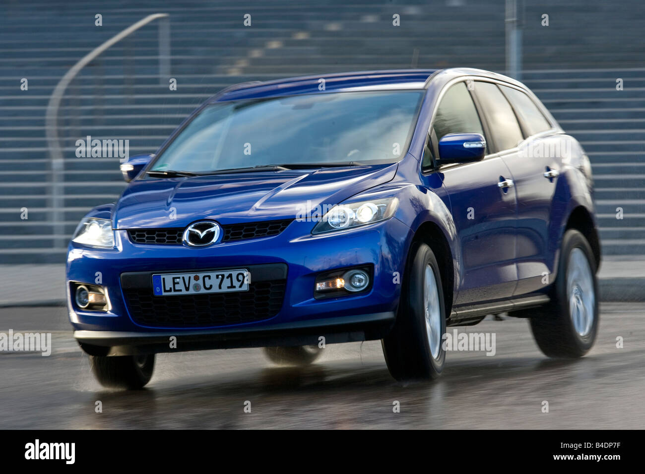 Mazda CX-7 2.3 MZR DISI Expression, model year 2006-, blue moving, diagonal from the front, frontal view, City - Stock Image