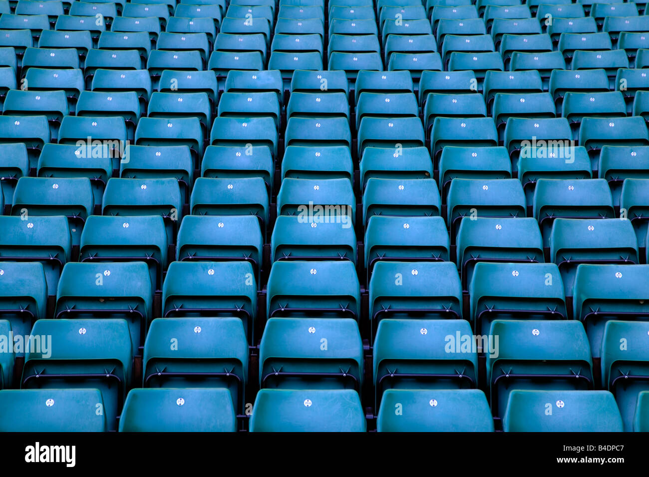 Rows of empty blue seats in a sports stadium - Stock Image