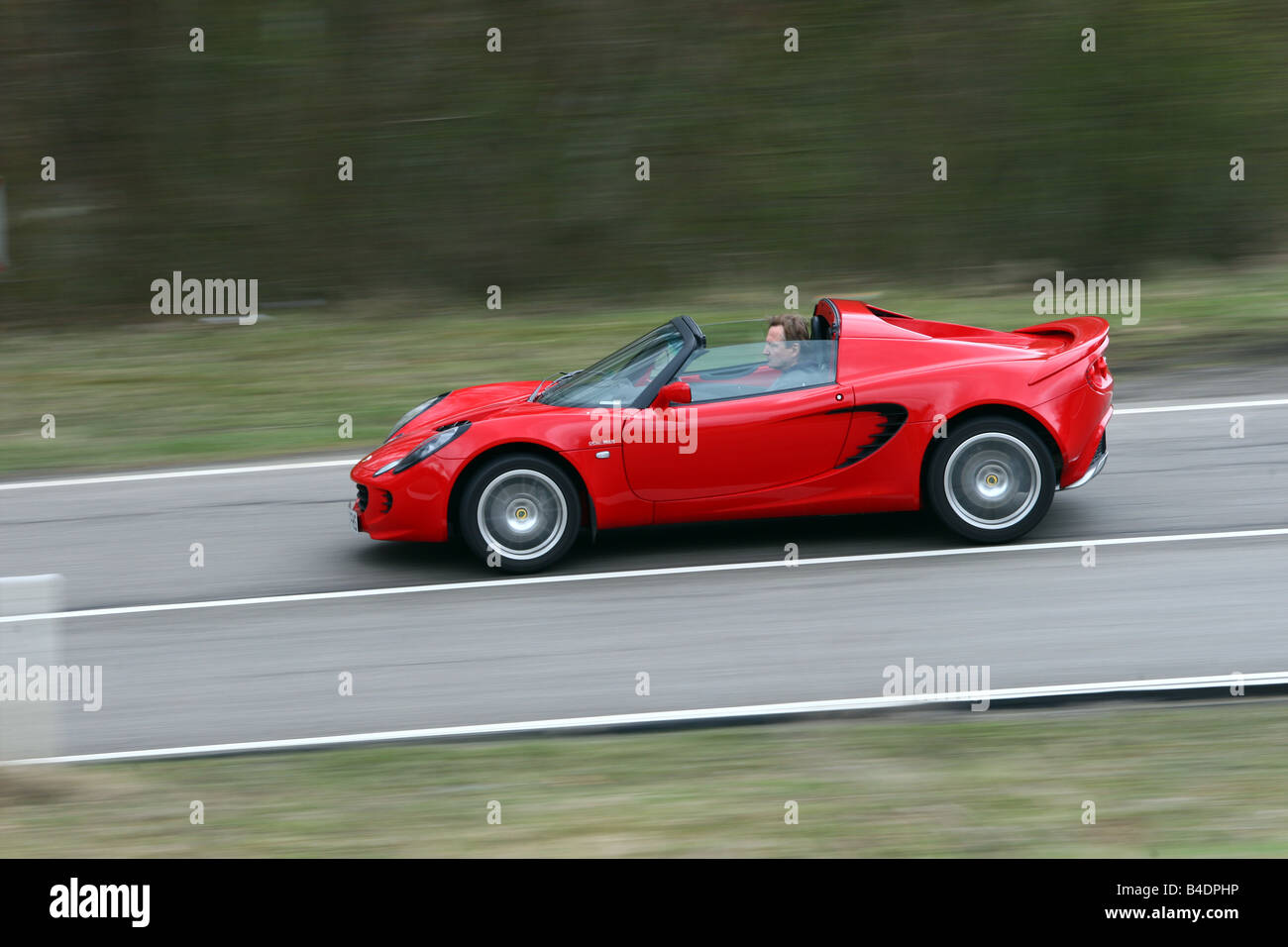 https://c8.alamy.com/comp/B4DPHP/lotus-elise-sc-model-year-2008-red-driving-side-view-country-road-B4DPHP.jpg