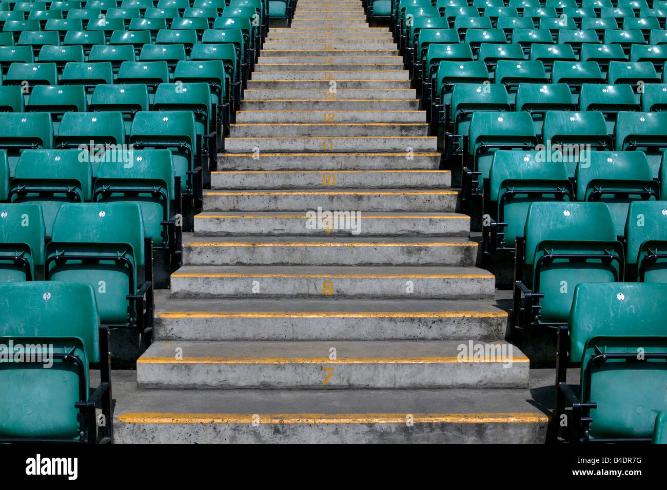 Numbered steps in a sports stadium in between the green pastic seating Stock Photo