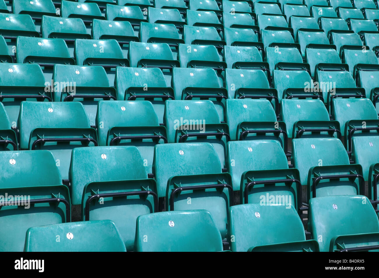 Rows of empty green plastic chairs in a sports stadium - Stock Image