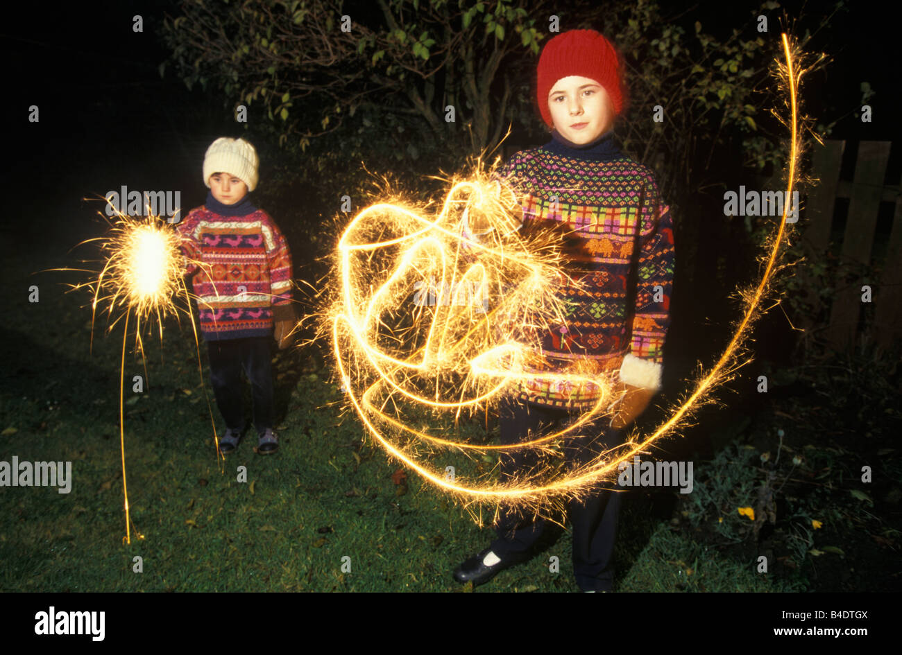 2 girls playing with sparklers on bonfire night - Stock Image