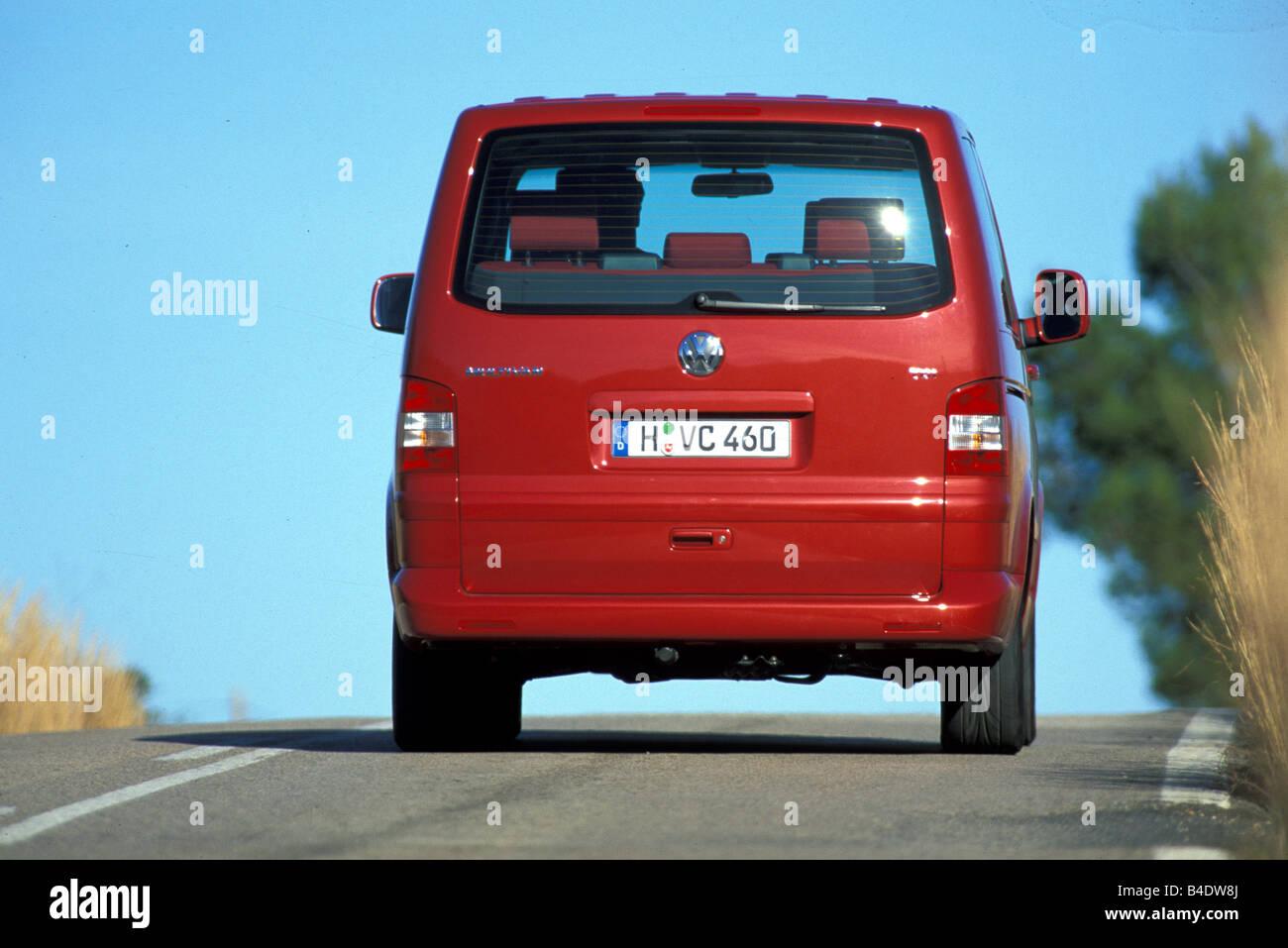 Car, VW Volkswagen Multivan T5 2.5 TDI, Van, model year 2003-, red, driving, diagonal from the back, rear view, - Stock Image
