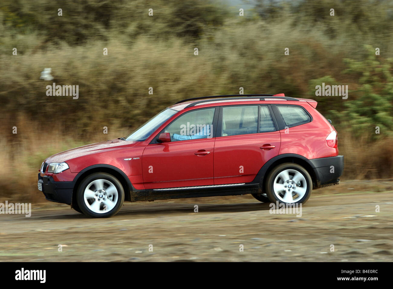 Car, BMW X3, cross country vehicle, model year 2003-, red, FGHDS, driving, side view, offroad - Stock Image