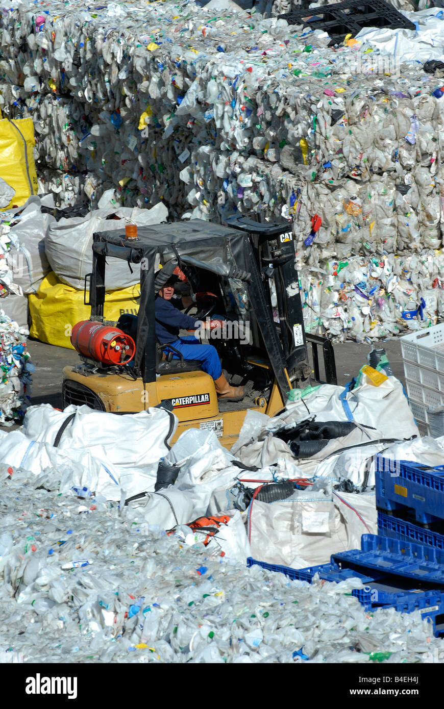 Gas powered forklift truck operating in the storage yard of a waste plastic recycling facility - Stock Image